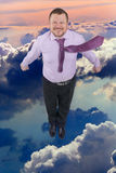 Businessman flying up over cloud sky in background Stock Photo
