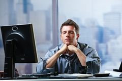 Businessman focusing on problems in office. Exhausted businessman focusing on solution of problems sitting at office desk eyes closed stock photo