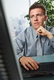 Businessman focusing on problems in office. Busy businessman focusing on solving problems sitting at desk in office stock image
