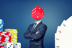 A businessman with folded arms stands with a large casino dice instead of his head. royalty free stock image