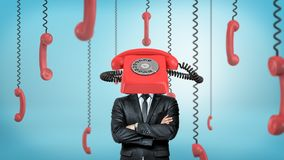 A businessman with folded arms stands surrounded by phone receivers and with one red retro phone placed on his head. Business communication. Always on phone stock photo