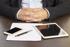 Businessman folded his hands at the desk close-up. stock photo
