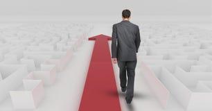 Businessman following red arrow walking through maze. Digital composite of Businessman following red arrow walking through maze Royalty Free Stock Photos