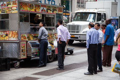 Businessman at food cart in New York Stock Images