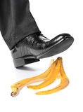 Businessman foot on a banana peel. Businessman foot about to slip and fall on a banana peel on white background Royalty Free Stock Photography