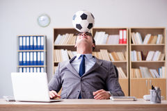 The businessman with football ball in office Stock Photography