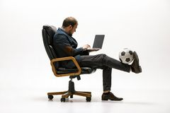 Businessman with football ball in office. Soccer freestyle. Concept of balance and agility in business. Manager perfoming tricks sitting on chair and working stock images