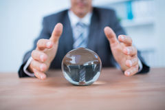 Businessman forecasting a crystal ball. In the office Royalty Free Stock Photos
