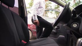 Businessman In Formal Attire Sits Behind The Wheel. Young Male Businessman In Formal Attire Sits Behind The Wheel Of His Luxury Car. Concept Of Business And Time stock video footage