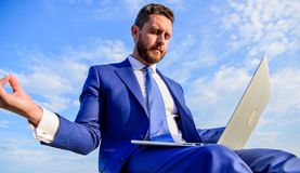 Businessman formal suit with laptop meditating outdoors. Man try keep his mind clear. Entrepreneur find minute relax and. Meditate. Work online can be annoying royalty free stock photography