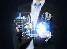 A businessman in formal suit is pushing out the element on the hologram with business icons. Stock Photo