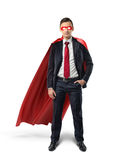 A businessman in a formal suit, a red flowing cape and a red eye mask with one hand in his pocket in front view. Royalty Free Stock Photos