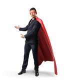 A businessman in a formal suit, a red flowing cape and a red eye mask showing something behind him. Advertisement and promotion. Business and sales royalty free stock images