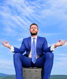 Businessman formal suit sit on briefcase and meditating outdoors. Man try to keep his mind clear. Relaxation technique. Keeping calm inside his soul royalty free stock photography