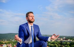 Businessman formal suit sit lotus pose and meditating outdoors. Man try to keep his mind clear. Relaxation technique. Keeping calm inside his soul royalty free stock image