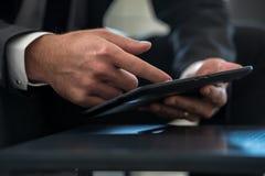 Businessman in formal suit navigating digital tablet Royalty Free Stock Images