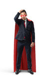 A businessman in a formal suit and superhero cape and mask looking doubtful and holding his head. Stock Photos
