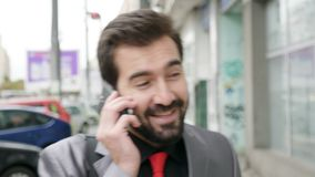 Businessman in formal suit walking on the street and talking on the phone stock video