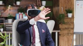 Businessman in formal suit wearing a virtual headset. In modern creative office stock video footage