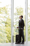 Businessman in formal wear holding trolley Royalty Free Stock Photos