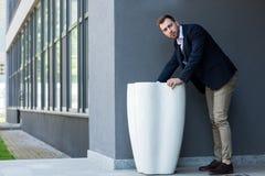 businessman in formal wear standing at garbage bin near office stock photo