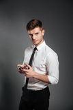Businessman in formalwear holding mobile phone and looking at camera. Serious young businessman in formalwear holding mobile phone and looking at camera isolated Royalty Free Stock Photos