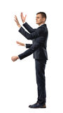 A businessman with four hands making grabbing motions and a fist in side view on white background. Royalty Free Stock Photos