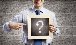 Businessman with frame. Young smiling businessman holding chalkboard with question sign Stock Images