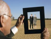 Businessman Framing Couple In Desert Stock Photo