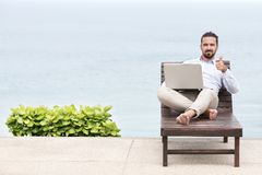 Businessman freelance on beach with laptop. Showing ok sign. Copy space for advertising stock image