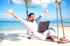 Businessman freelance on beach with laptop. Businessman wearing white freelance sitting on beach swing with laptop stock photography