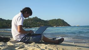 Businessman freelancer sitting and working on the beach with laptop. slow motion. 1920x1080. Businessman sitting and working on the beach with laptop. slow stock video