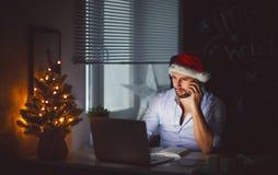 Businessman freelancer tired, asleep working at computer at Chri. Business man businessman freelancer tired, asleep working at computer at Christmas Stock Photos