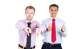 Businessman, friends; one being excited, smiling, showing thumbs-up, the other serious, concerned, showing thumbs down Stock Images