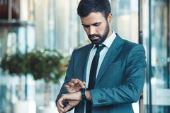 Businessman in a fromal suit in a business center checking time stock photo