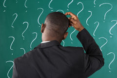 Businessman In Front Of Chalkboard With Question Mark Sign Stock Photography
