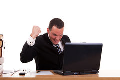 Businessman in front of the computer, arm raised Royalty Free Stock Photos