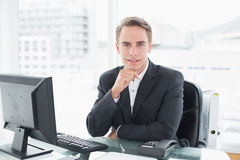 Businessman in front of computer at office desk Stock Photos