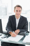 Businessman in front of computer writing document at office desk Royalty Free Stock Photography