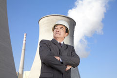 Businessman in front of cooling tower Royalty Free Stock Image