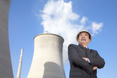 Businessman in front of cooling tower Royalty Free Stock Images