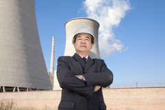 Businessman in front of cooling tower Stock Image