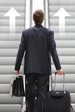 Businessman front escalator with arrows Royalty Free Stock Photo