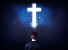 Businessman in front of a glowing cross Royalty Free Stock Photo