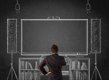 Businessman in front of a home cinema system Royalty Free Stock Image