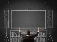 Businessman in front of a home cinema system. Young businessman sitting and enjoying home cinema system sketched on a chalkboard royalty free stock image