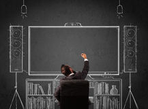 Businessman in front of a home cinema system. Young businessman sitting and enjoying home cinema system sketched on a chalkboard Stock Photo