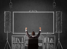 Businessman in front of a home cinema system. Young businessman sitting and enjoying home cinema system sketched on a chalkboard Royalty Free Stock Images