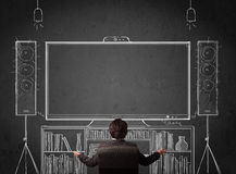 Businessman in front of a home cinema system. Young businessman sitting and enjoying home cinema system sketched on a chalkboard Stock Photos
