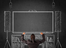 Businessman in front of a home cinema system. Young businessman standing and enjoying home cinema system sketched on a chalkboard Royalty Free Stock Image